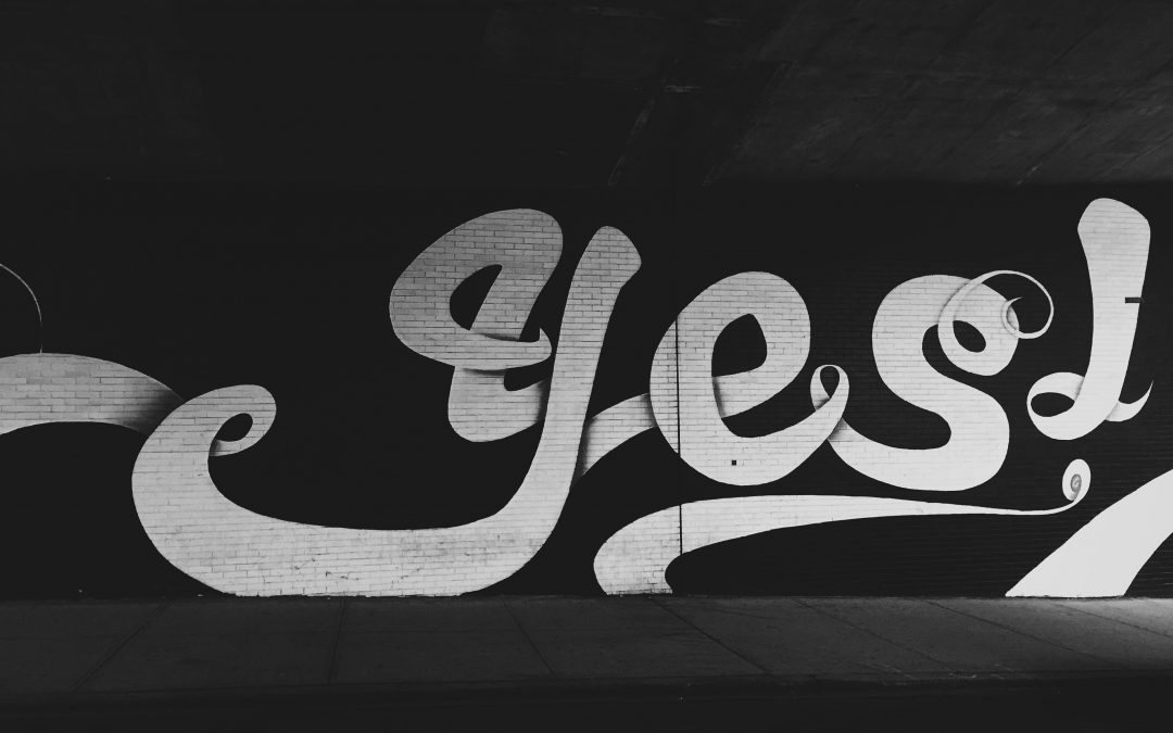 Picture of 'Yes!' written on a brick wall