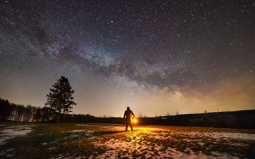 Photo of person holding fire underneath the night sky